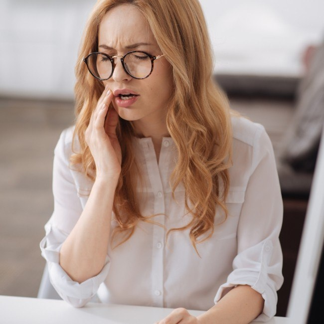 Woman covering her mouth before wisdom tooth extraction