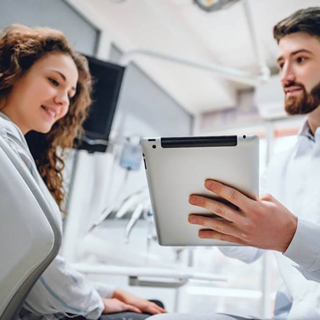 Smiling man talking to oral surgeon about wisdom tooth extraction