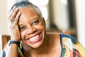 woman with a beautiful smile thanks to implant retained dentures in houston