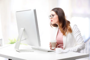 Woman staring at her computer while holding her coffee cup