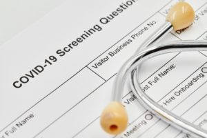 oral surgeon's COVID-19 screening questionnaire form under stethoscope