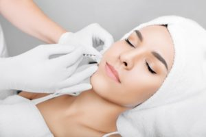 Relaxed woman receiving dermal filler from oral surgeon in Houston