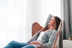 Woman relaxing at home after dental implant surgery