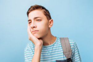 Teenage boy in striped shirt experiencing wisdom tooth pain